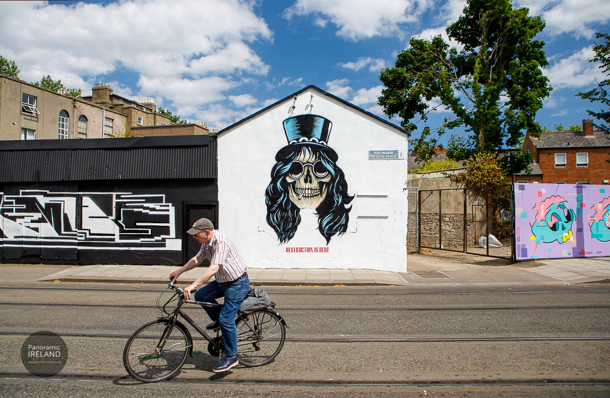 A man on a bicycle passes street art of Slash from Guns N' Roses in Dublin on a sunny day