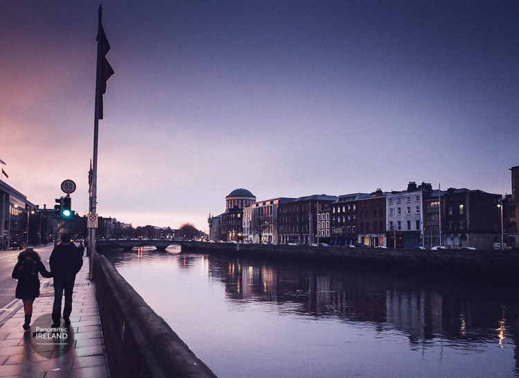 A couple walk along the quays of Dublin as evening approaches