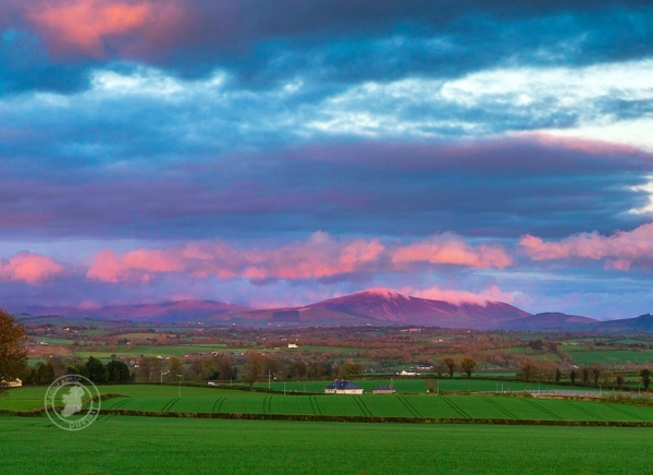 Pink, wisping clouds above the green landscapes of Ireland