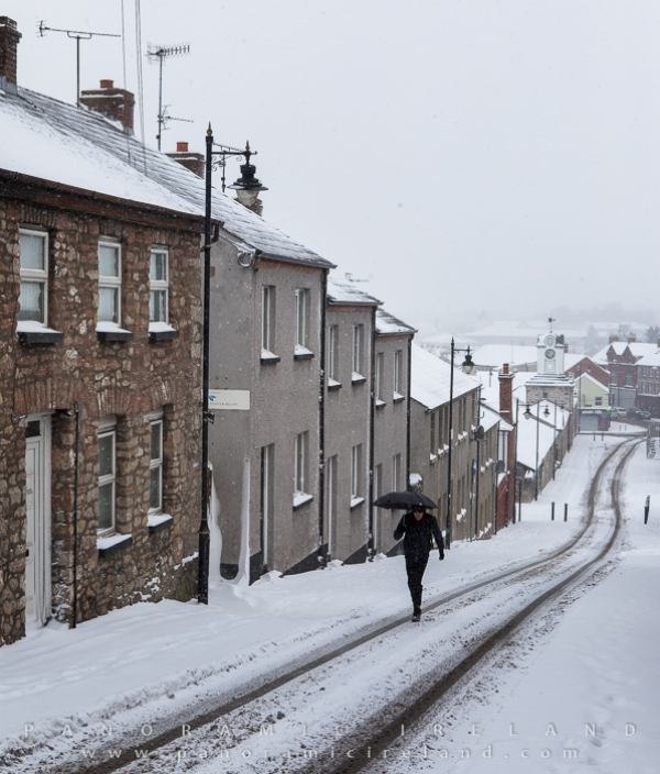 Man walks up snow-covered street in Armagh during Storm Emma / Beast from the East