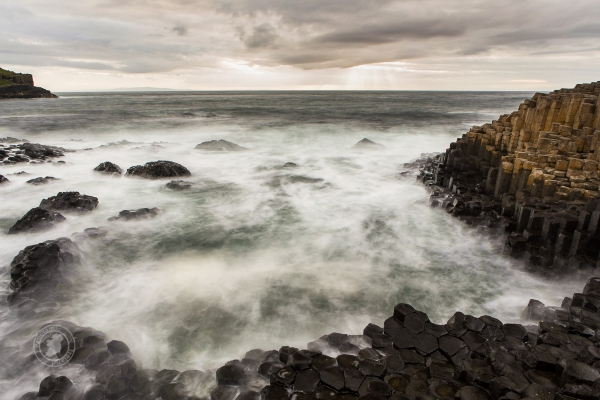 Northern Ireland's Giant's Causeway with sun rays and cloudy sky