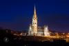 Cobh's St. Colman's Cathedral after dark with night illumination against a blue sky