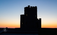 Silhouette of tower at sunset in Ireland - Guess the location.