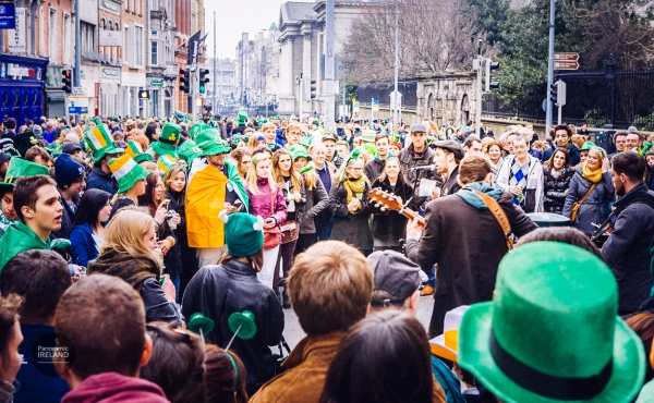 Saint Patrick's Day on Grafton Street, Dublin - a crowd surrounds buskers playing guitars