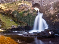 Waterfall under old stone bridge in the west of Ireland